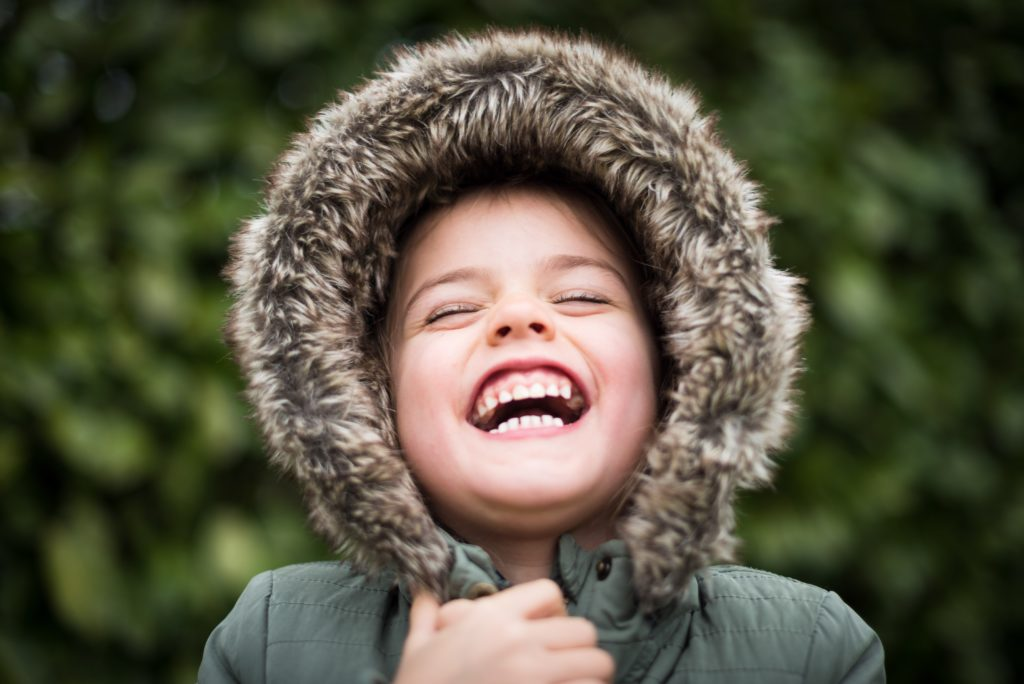 Image of child wearing a warm coat and smiling.